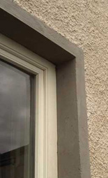 limewashed render and dash with silicate painted lime window surrounds with concrete sills