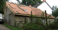 exterior view of repaired barn with cut and pitched roof